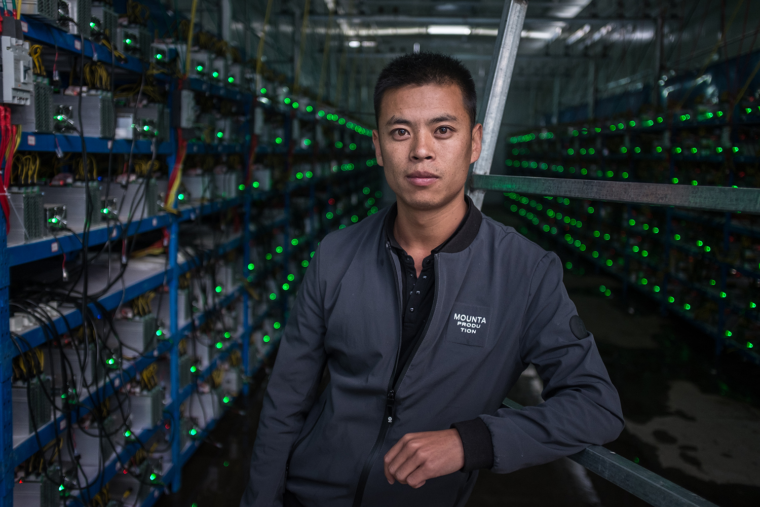 A 29-year-old Tibetan named Kun poses in between aisles of mining machines, September 26, 2016. Kun is the mine's manager as well as one of its investors. He learned about Bitcoin through a friend and started investing in 2015.