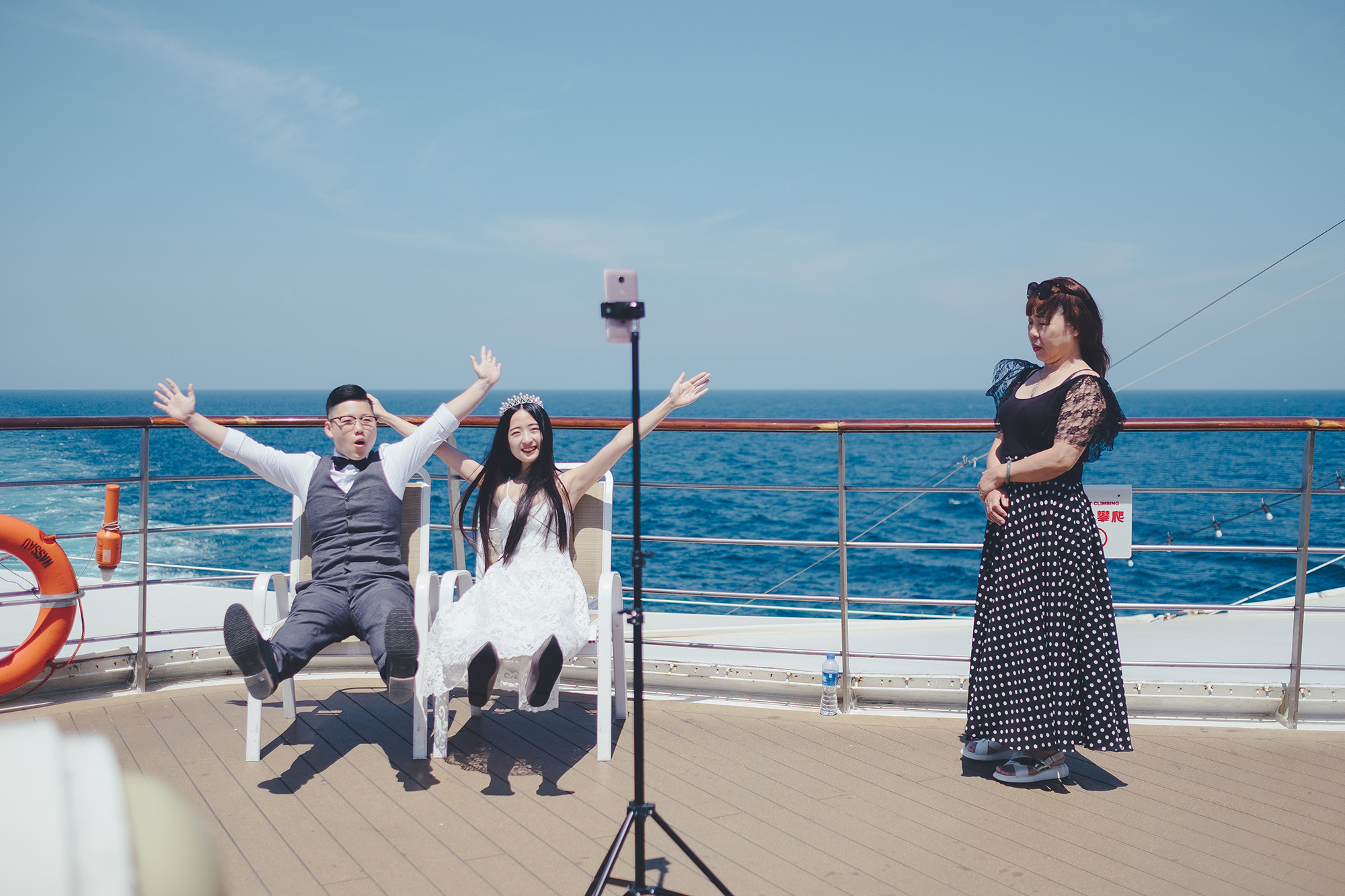 In the morning, Yang and Chen pose for wedding photos on the deck. Chen's mother, Mrs. Zheng (right), who is the couple's only parent on board, looks on.