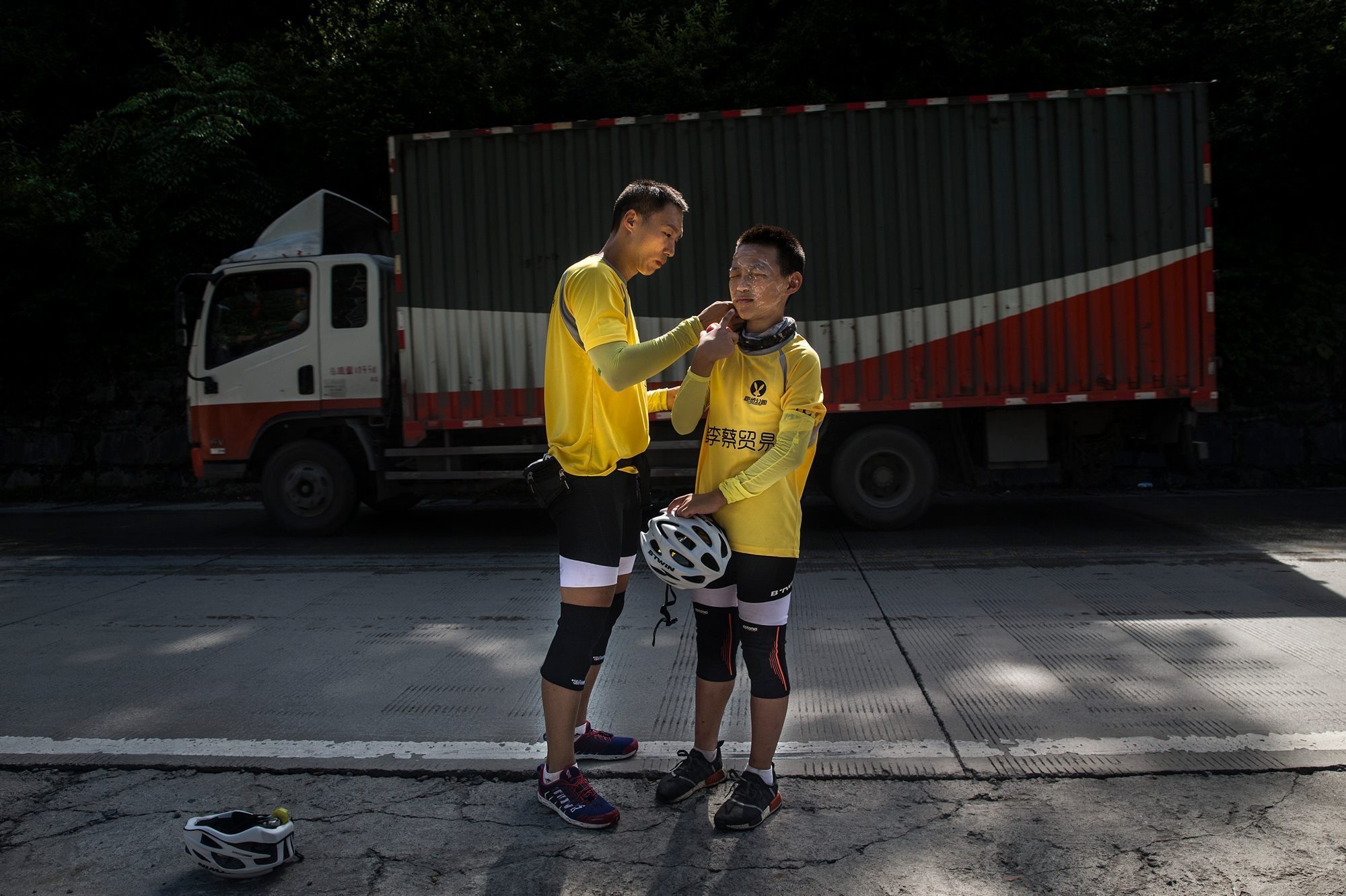 Chao applies sunscreen to Runxi's face on Mount Erlang, in Tianquan county of Ya'an city, Sichuan province, July 17. Their route that day traverses the mountain through a 2.6-mile tunnel.