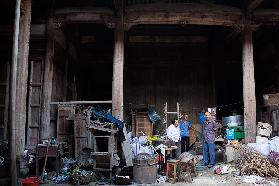 "Wang Shouchang (right)  looks out at the main courtyard of Mingxian Hall with its caretaker, Wang Changfa (center), seventy-two, and his wife. Above the clutter, the elegant timbered roof beams remain intact. Wang Changfa began renting Mingxian hall from the government at 20 RMB per year in 1982. Since then, he and other villagers have gradually transformed the building into a communal storage space and barn for Wang Changfa's pigs and chickens. ""The government has long stopped charging me the rent,"" Wang says,  ""but I still have the responsibility to keep [the hall] standing."""