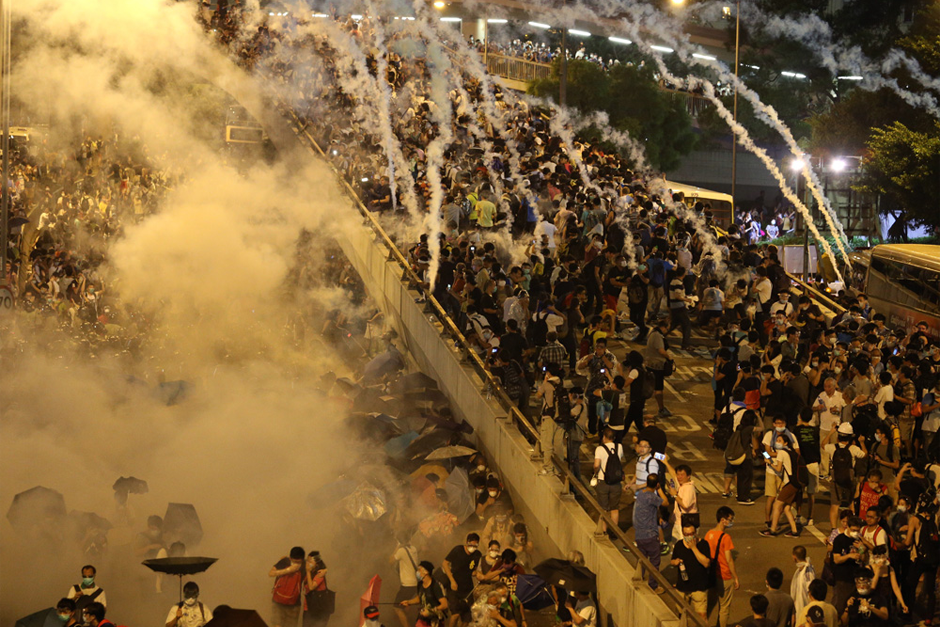 Police fire tear gas on pro-democracy demonstrators near the Hong Kong government headquarters. Parts of central Hong Kong came to a standstill September 28 in a dramatic escalation of protests that have gripped the semi-autonomous Chinese city for days. (Photo by Aaron Tam/AFP/Getty Images)