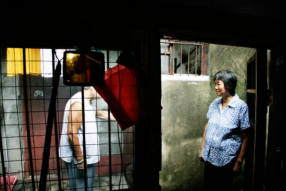 Ms. Ding stands in a narrow alley of Lane 1290 West Yan'an Road talking with her neighbor in the summer of 2009. Ms. Ding has lived in the same neighborhood for more than fifty years. Hidden from the outside world in a deteriorating section of the city, residents in this area consider themselves forgotten in the midst of Shanghai's massive ongoing facelift and nonstop development.