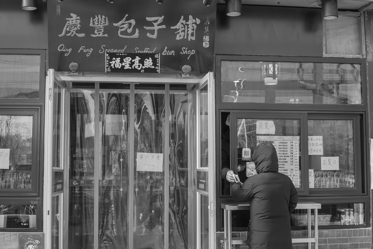 A customer orders food through a window at Qingfeng Baozi restaurant on Xuanwumenwai Avenue, February 18, 2020.