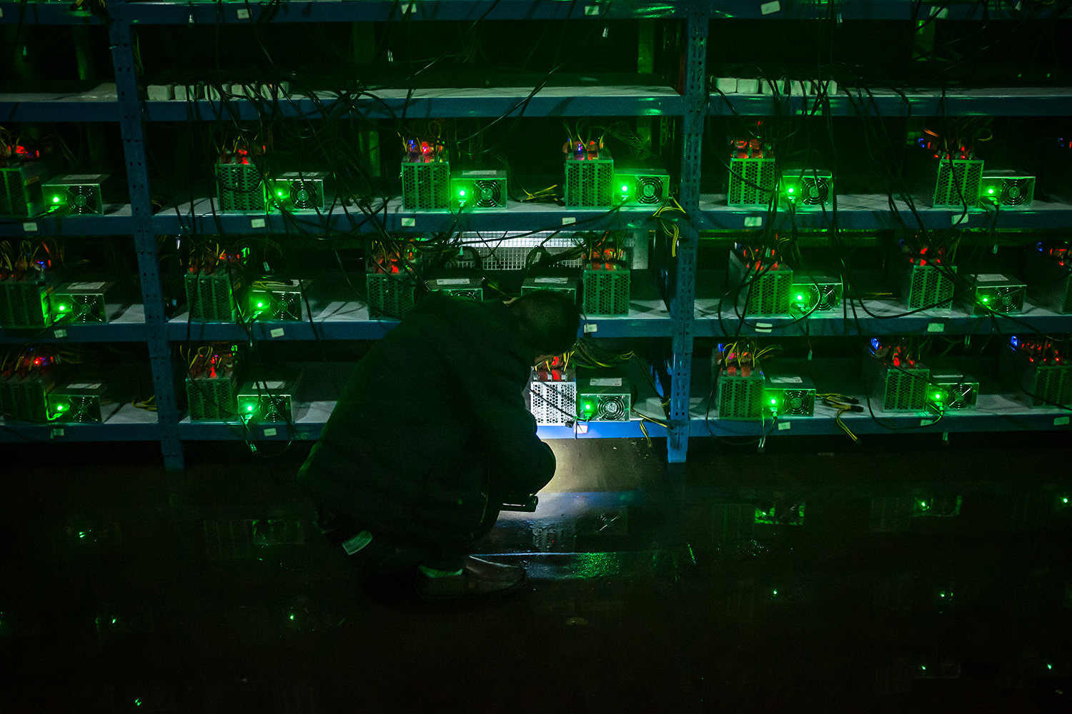 "Huang, 25, Kun's brother, inspects a malfunctioning mining machine during his night shift, September 26, 2016. Miners can check a machine's condition and operations using phones and personal computers. For most issues, they can simply restart a machine. ""If it's a complicated problem, we just ship it to the factory and let them fix it,"" Huang said."