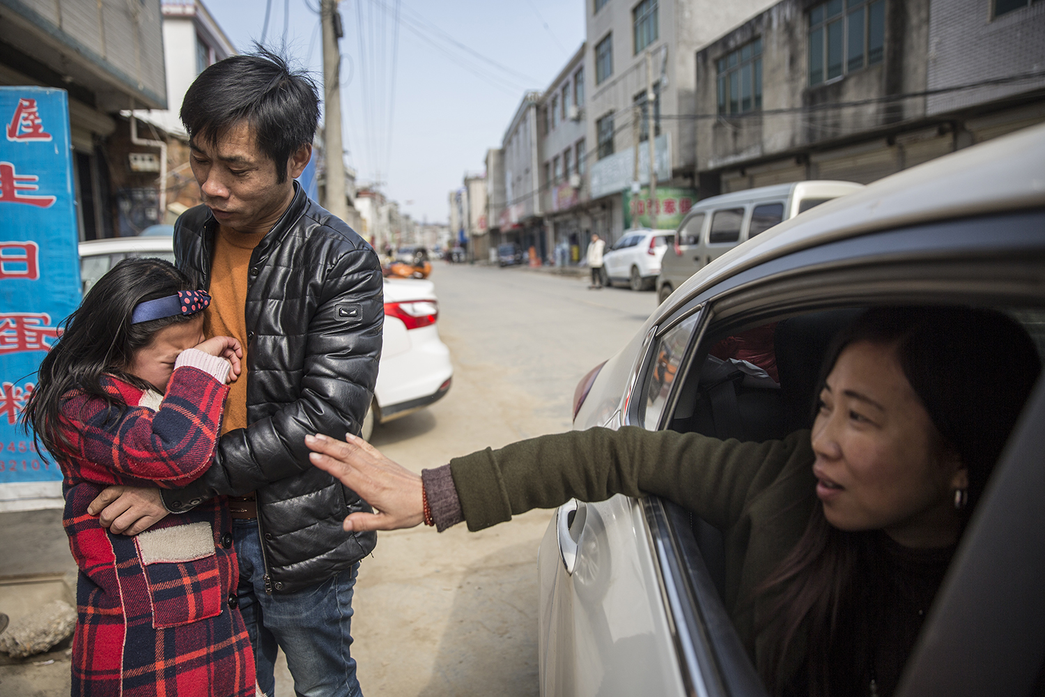 "February 11, at the end of the Lunar New Year holiday, nine-year-old Lü Siqi cries as her mother waves goodbye in Xiangshuitan township, Jiangxi province. Siqi's parents both work in Hangzhou and visit her twice a year—once on the Lunar New Year and once on her birthday. She is among an estimated 9 million so-called ""left-behind children"" currently living in the Chinese countryside without their parents. (Chen Ronghui/Sixth Tone)"