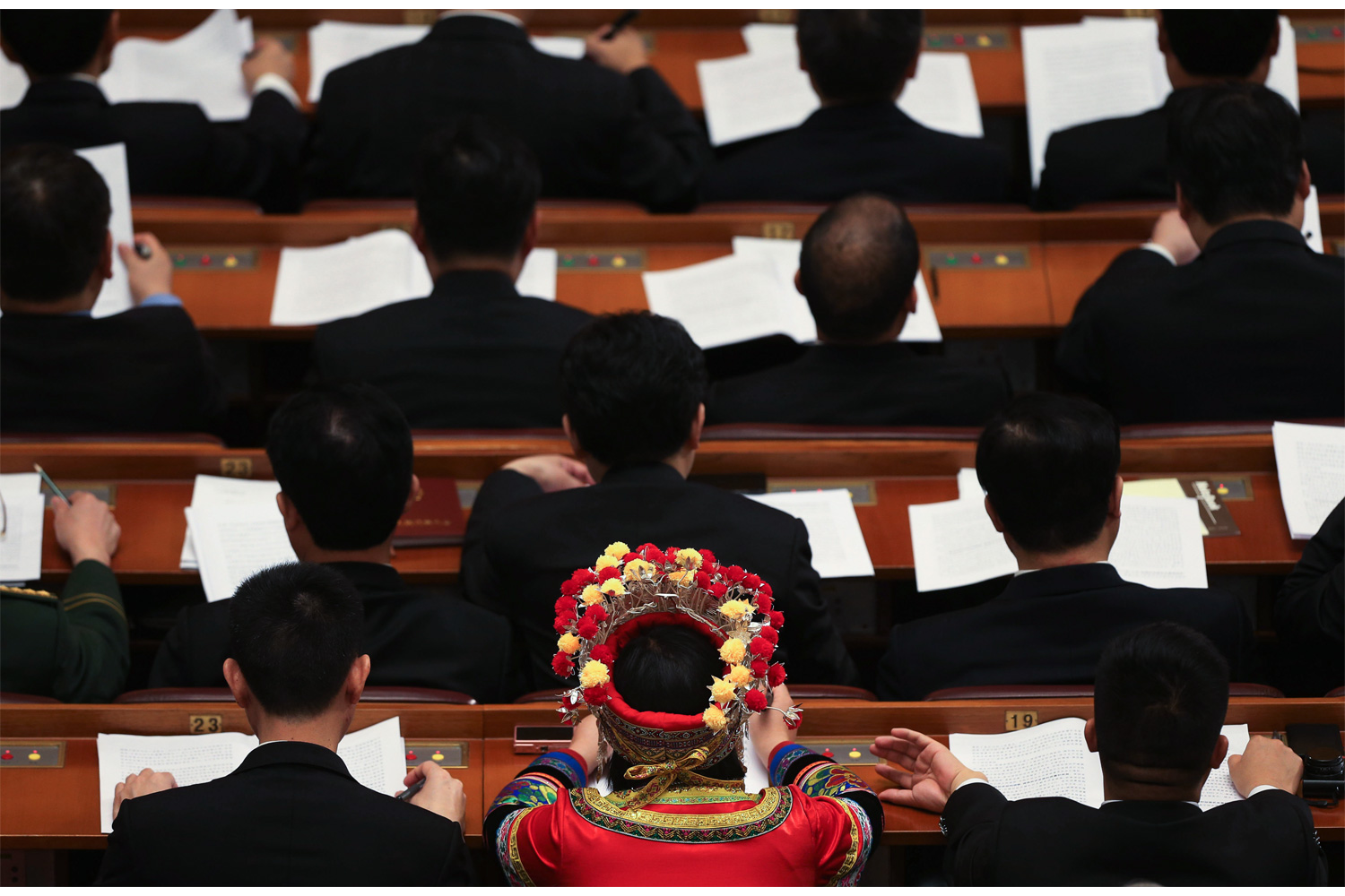 A female deputy sits among her fellow deputies as they listen to a report on the work of the government inside the Great Hall, March 5, 2013.