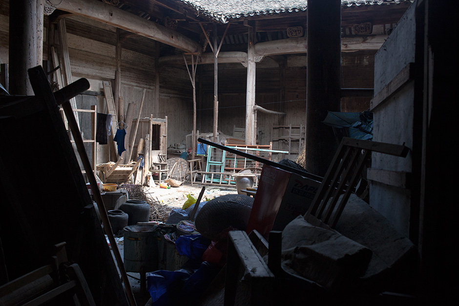 "Fallen beams, window frames, and forgotten furniture obstruct the passage between the back room and inner courtyard of Mingxian Hall. ""In my lifetime, people have never performed any rituals in ancestral halls in our village,"" said Wang Shouchang. He says the last he heard of these customs was from elderly relatives during his childhood, six decades ago. In the nearby towns of Xidi and Hongcun, ancestral halls and other historic buildings are largely intact and UNESCO heritage status has brought a lucrative stream of domestic tourists."