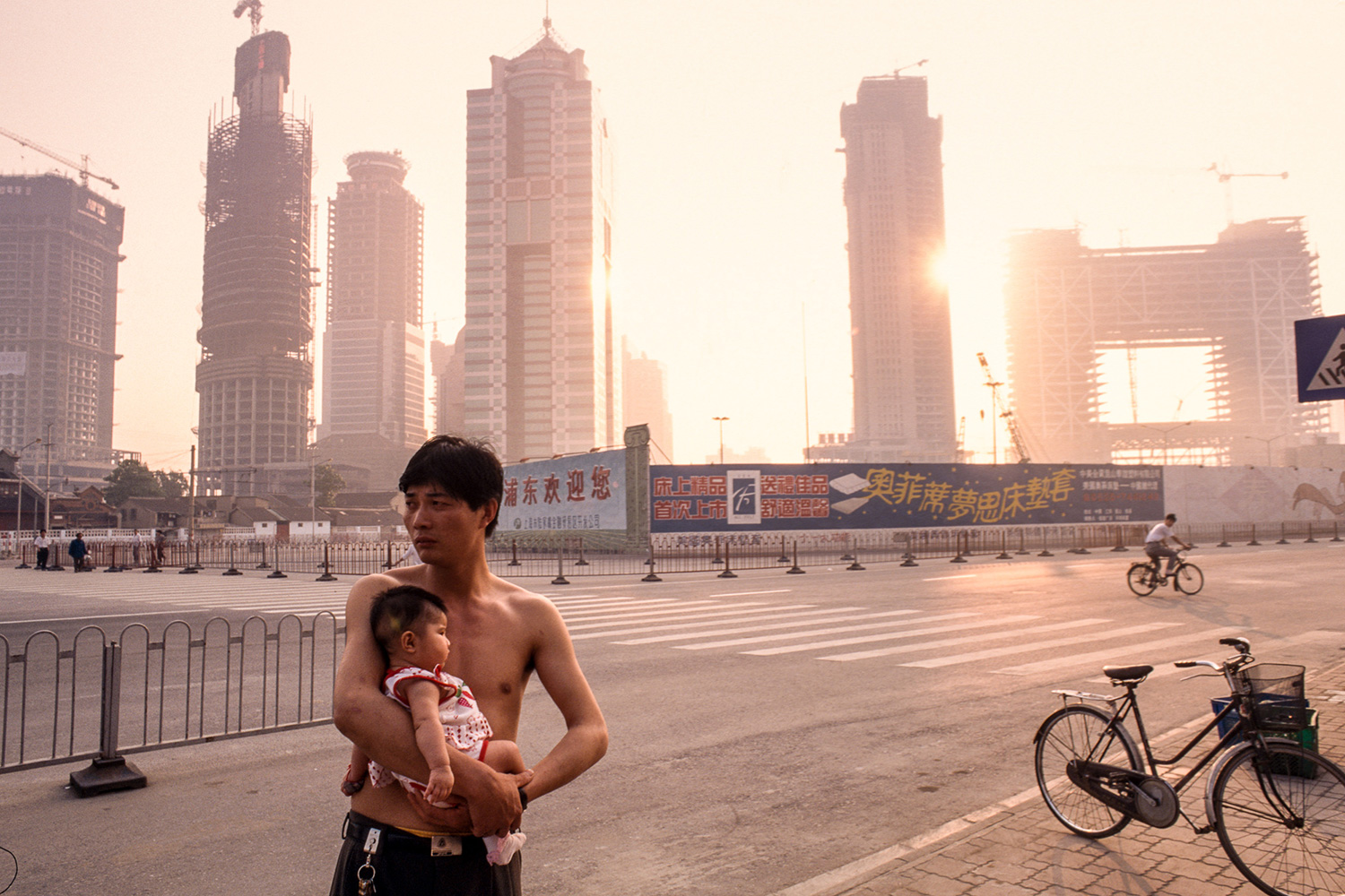 Outside his living quarters in Lujiazui, a construction worker from China's countryside holds his child, 1996.