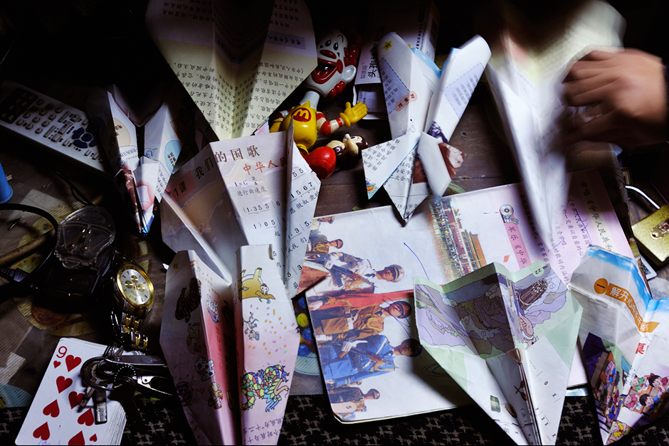 At Zhao Meifang's house, her kids and nephews use pages from old school books to make paper airplanes.