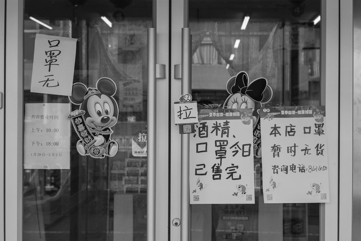 "A sign reading ""alcohol, masks sold out"" hangs on the door of a pharmacy on Di'anmen Street, January 29, 2020."