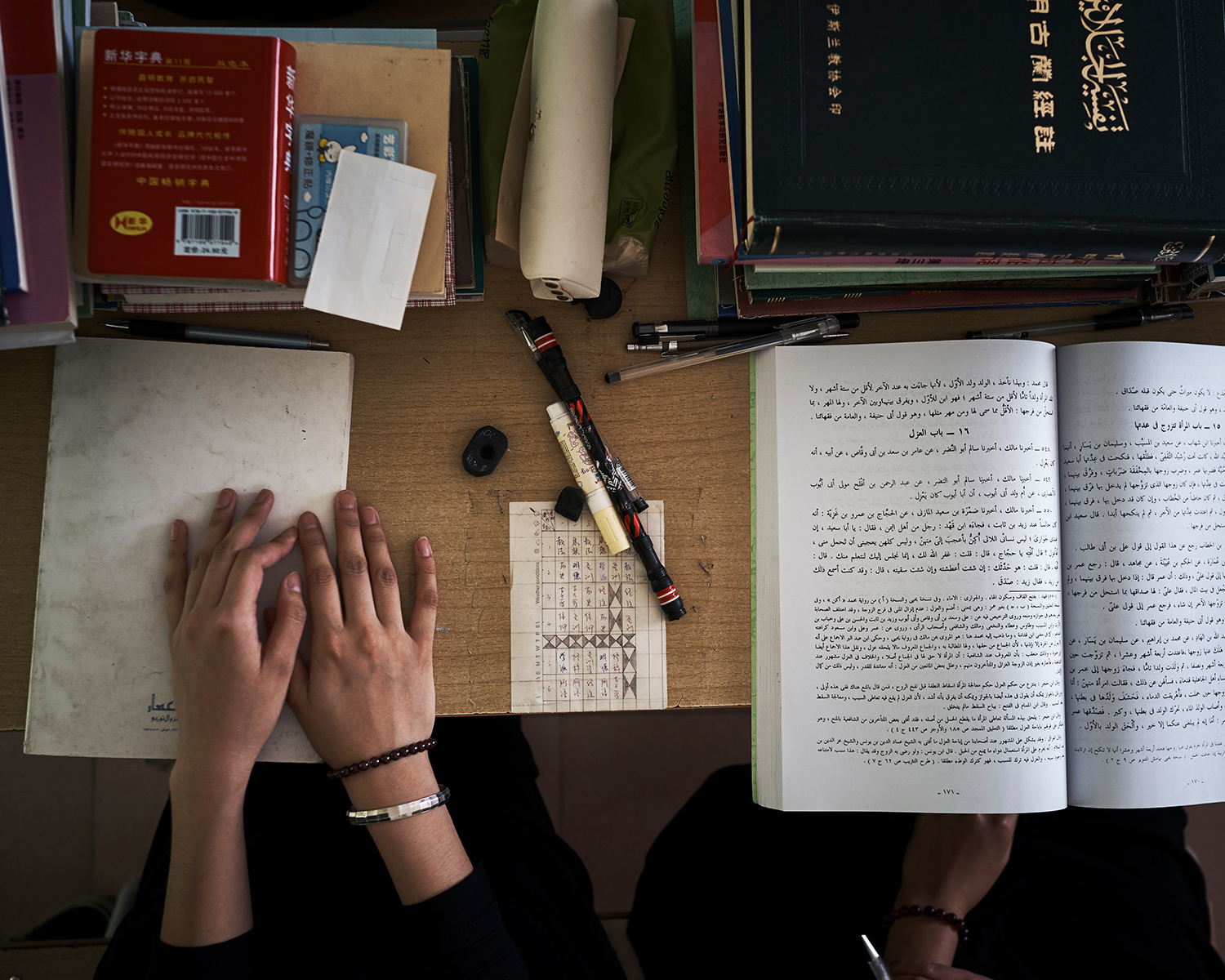 A student's desk at the Arabic school in Nanguan Mosque, June 2016. All textbooks are in Arabic, only a dictionary is in Chinese. After the 2014 knife attack in which several assailants from the Xinjiang Uighur Autonomous Region stabbed 31 people to death at a train station in Kunming, Yunnan's capital city, provincial authorities expelled Muslims who were not from Yunnan. Since then, only students from Yunnan have attended the school.