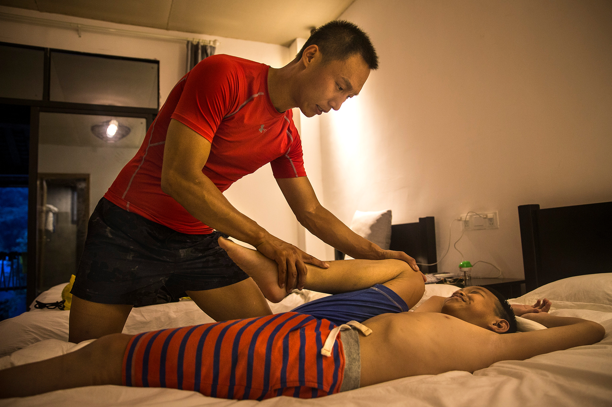 After an entire day biking, Chao helps Runxi stretch in a motel in Ya'an, July 15. Runxi's mother and Chao divorced when Runxi was three. Since then, Runxi has lived with his father and grandmother.
