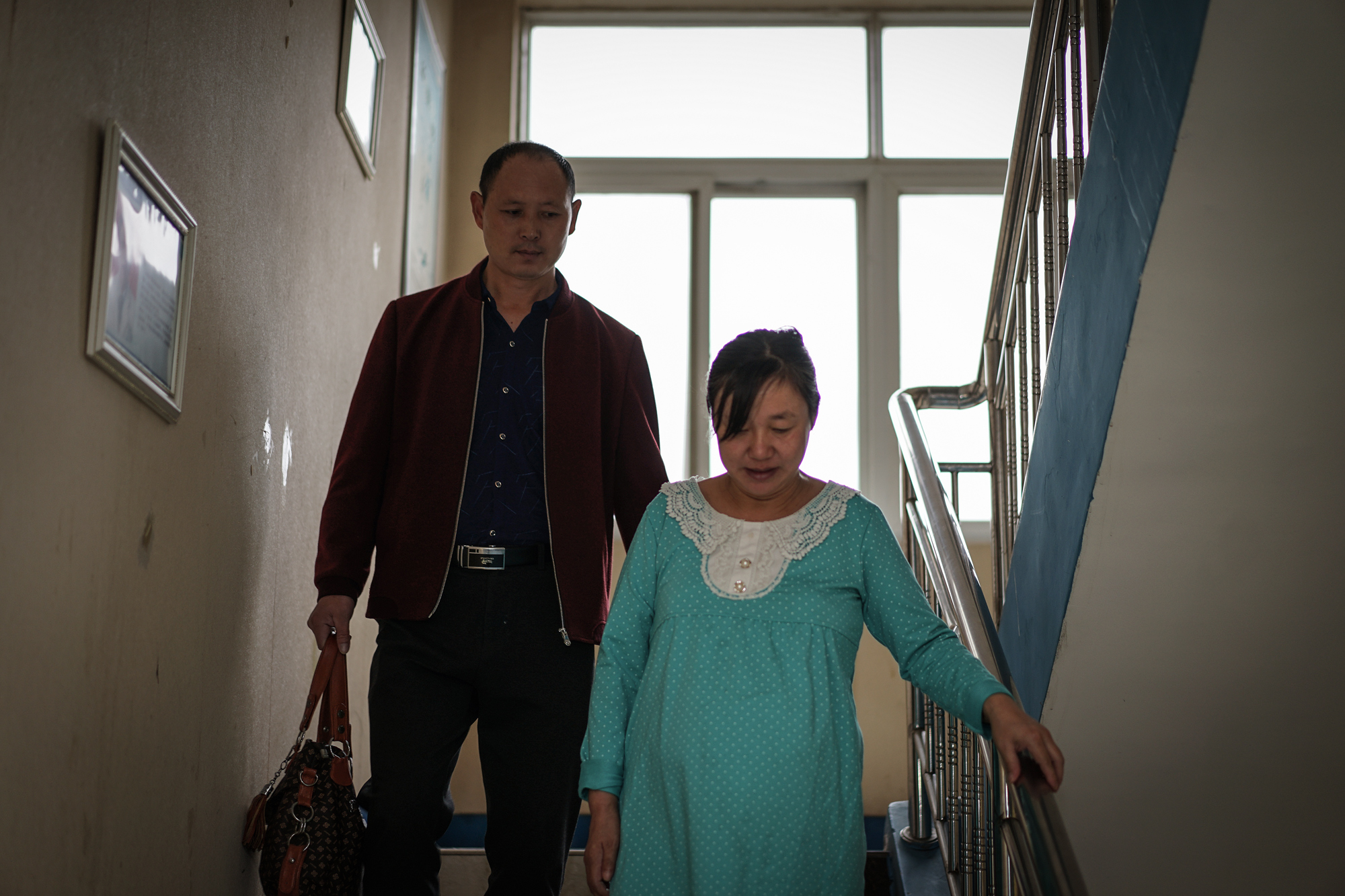 Fangguo watches Zhiying carefully walking downstairs at the hospital, in Wuhan, October 3, 2017. Even though carrying twins meant Zhiying and her babies faced higher health risks during pregnancy, they specifically tried to have twins when they started IVF because they hoped the children could take care of each other after the parents pass away.