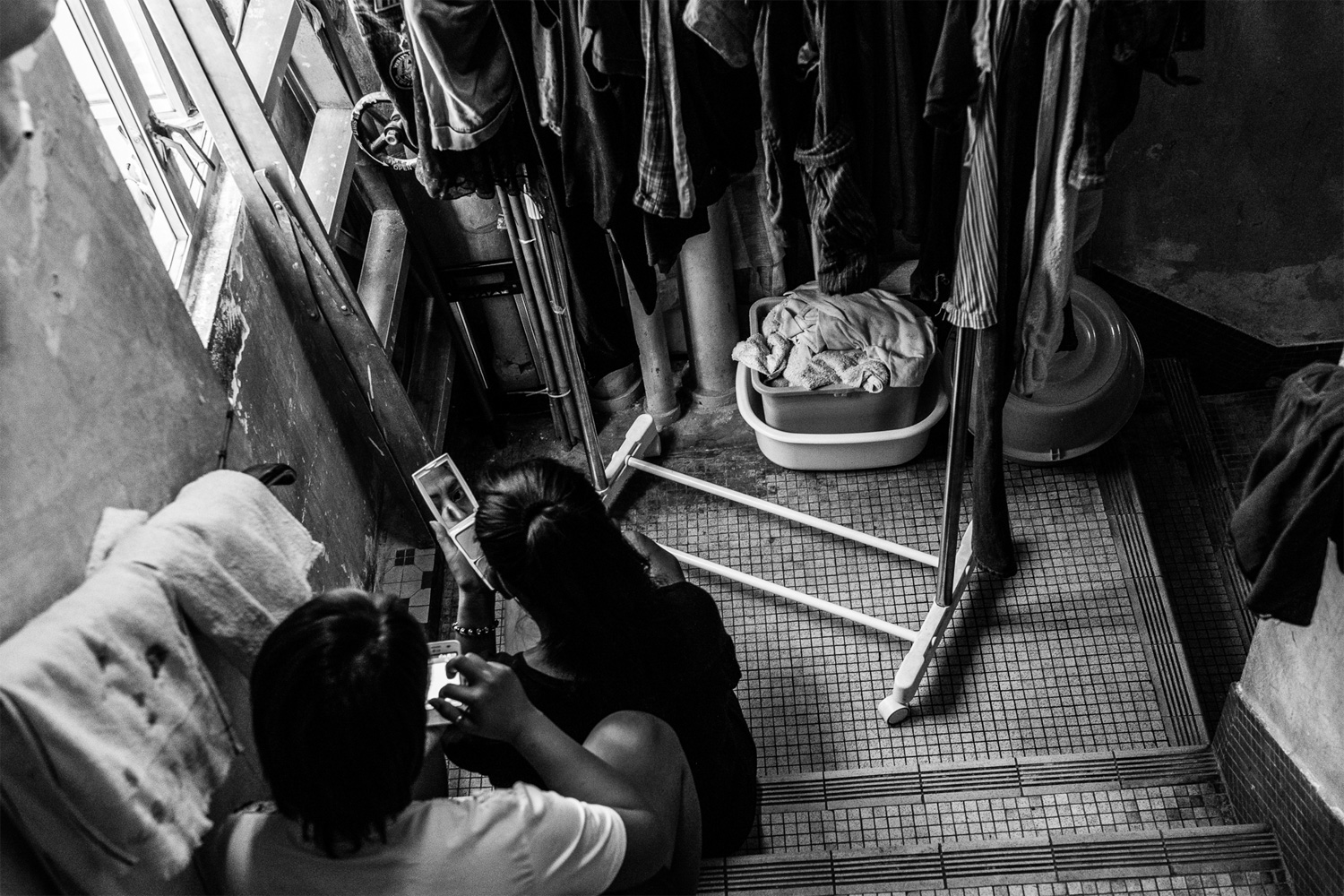 Sunarwi, left, and Kuryati, Indonesian domestic workers, take a break in the back staircase of the shelter. Most Indonesian workers complain that they are underpaid. According to Bethune House staff, Indonesians are paid less than other nationalities, and their income often falls below the minimum allowable wage level set by the Hong Kong government.