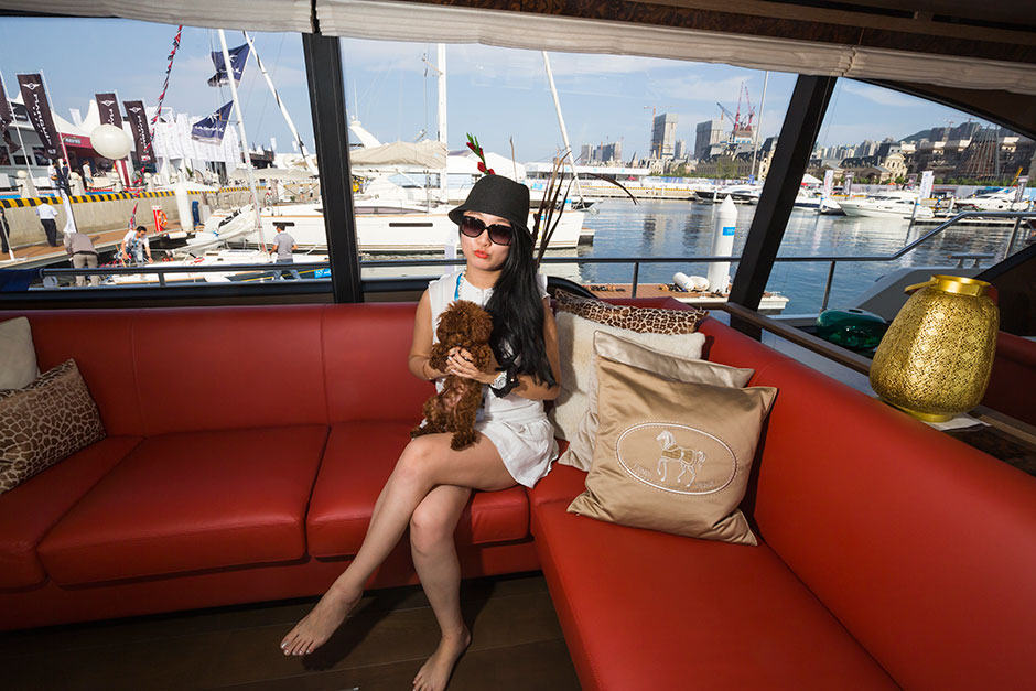 Zhang Luyi sits with her dog inside a yacht at SO! Dalian.