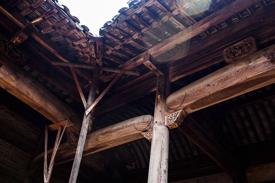 "Two wooden trestles, constructed and installed by the hall's caretaker Wang Changfa, hold up the front corner of the damaged Mingxian Hall. Wang says he hopes ""someone will take [the hall] away from me and repair it properly."""
