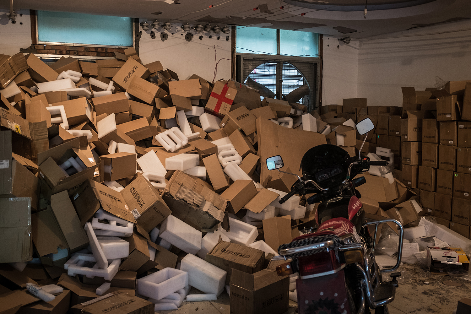 Packing boxes for mining machines pile up in an employee dormitory, September 26, 2016. Kun recently purchased new mining machines: the AntMiner S7 (U.S.$490) which has greater computing power than the  AntMiner S5 (U.S.$140) it would replace. 550 mining machines, a combination of S7 and S5 models, running 24 hours can mine 2.5 Bitcoins a day, according to Kun—worth around U.S.$6,400.