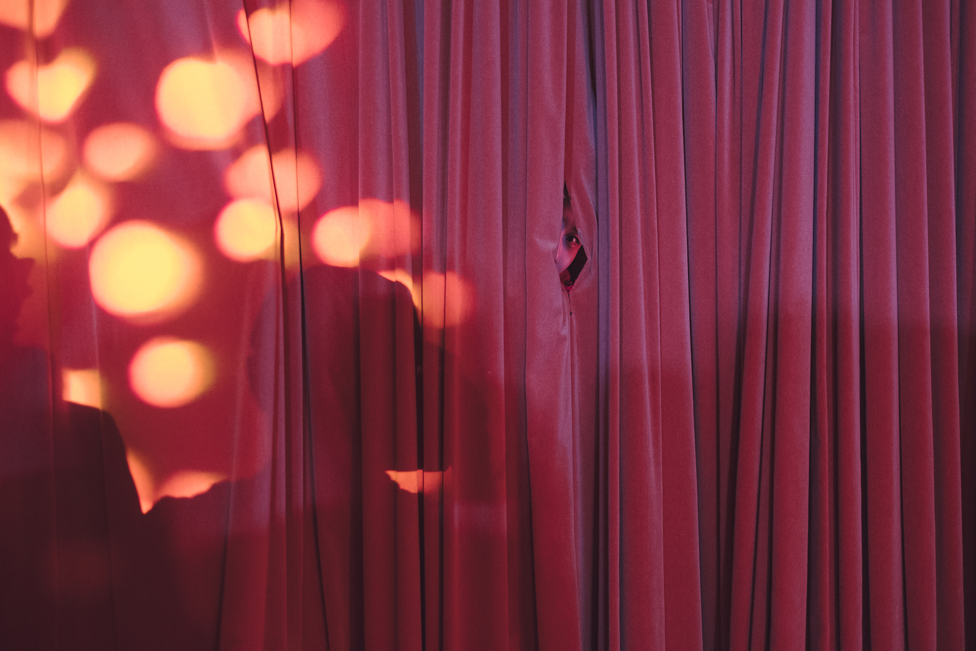 A guest peeks at the party crowd from behind a curtain. Same-sex marriage is not legal in China. This wedding has no official validity and is intended mainly as a chance to celebrate with family and friends. For many couples, it is more important to have the blessing of their parents than the blessing of the state.