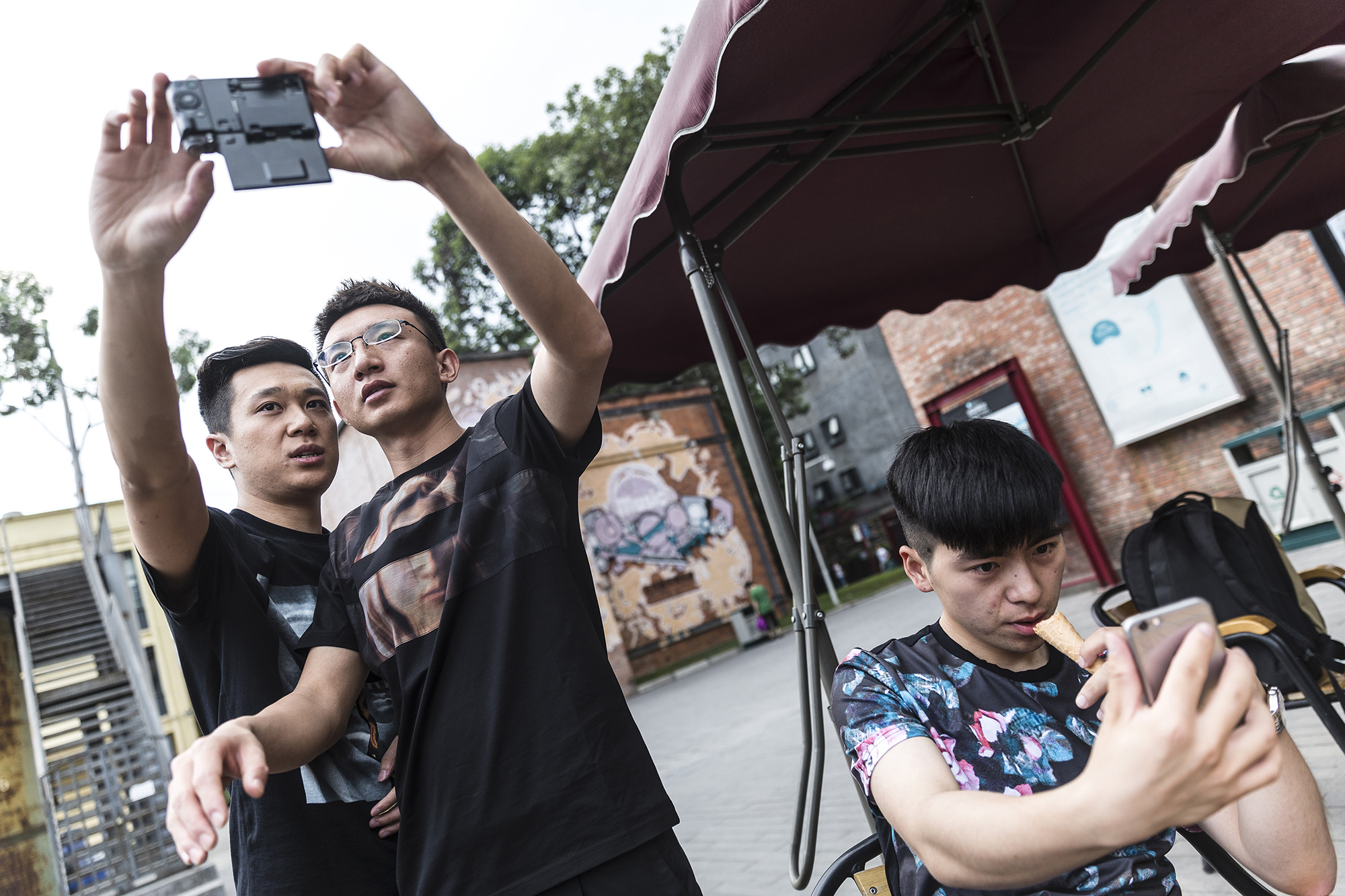 Brian shows a student how to take a better selfie at an art-themed park, May 16, 2015. According to the mentors, online profile photos should reflect a 'high-quality' lifestyle.