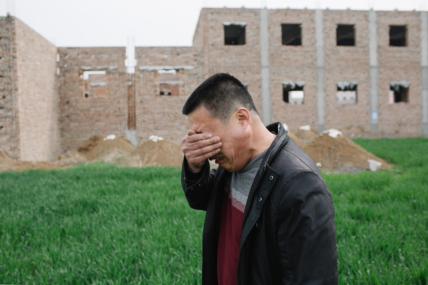 April 10, 50-year-old Zhao, owner of a shoe factory, covers his face to hide tears while discussing his worries about the future, in Anxin county, Hebei province. The Chinese central government announced the establishment of the Xiong'an New District on April 1. The district, designed to become a hub of economic development, encompasses the counties of Xiongxian, Anxin, and Rongcheng in Hebei. Many locals have feared their small businesses will be displaced by newcomers. (Wu Huiyuan/Sixth Tone)