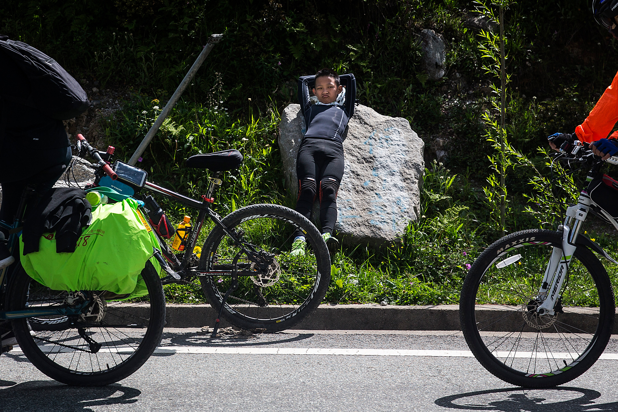 On the fifth day of the trip, Runxi rests on the side of the road because he is chafed from so many hours on his bike seat, in Zheduotang, Garze, Sichuan, July 19.