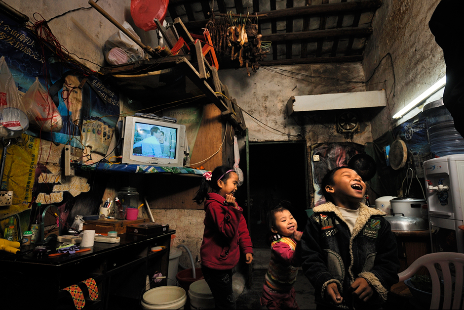 "Zhao Neng, right, plays in a neighbor's home. His parents, neither of whom got past middle school, save most of their income to send him and his older sister, Zhao Huan, to school back in more-affordable Chongqing. ""Of course I want to buy an apartment,"" says Zhao Xiaoyun, Neng's dad, ""but I don't have enough money."" Instead, his parents hope that Neng will attend college."