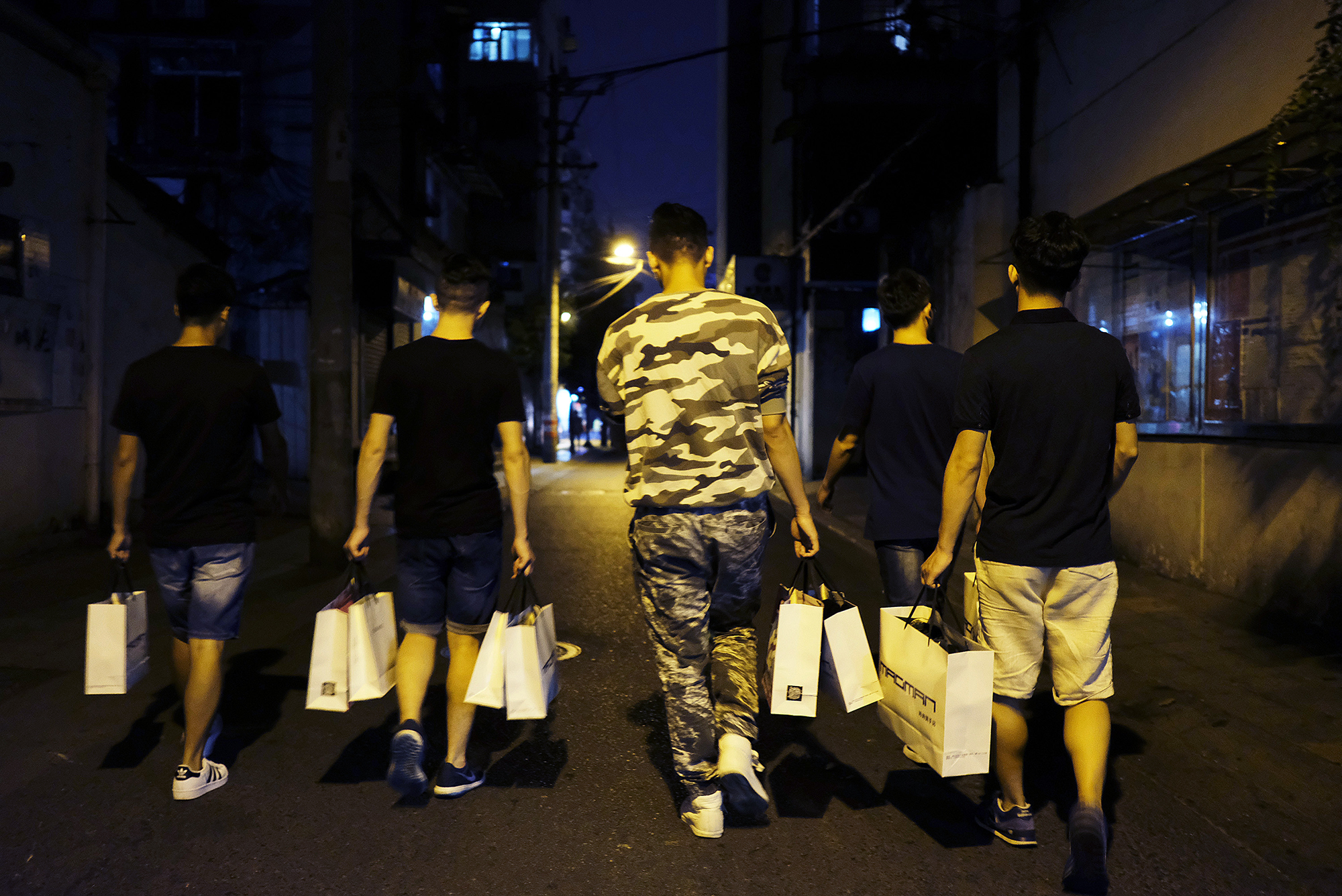 Students head back to their apartment after shopping with mentors on a bustling Chengdu commercial street, October 1, 2016.