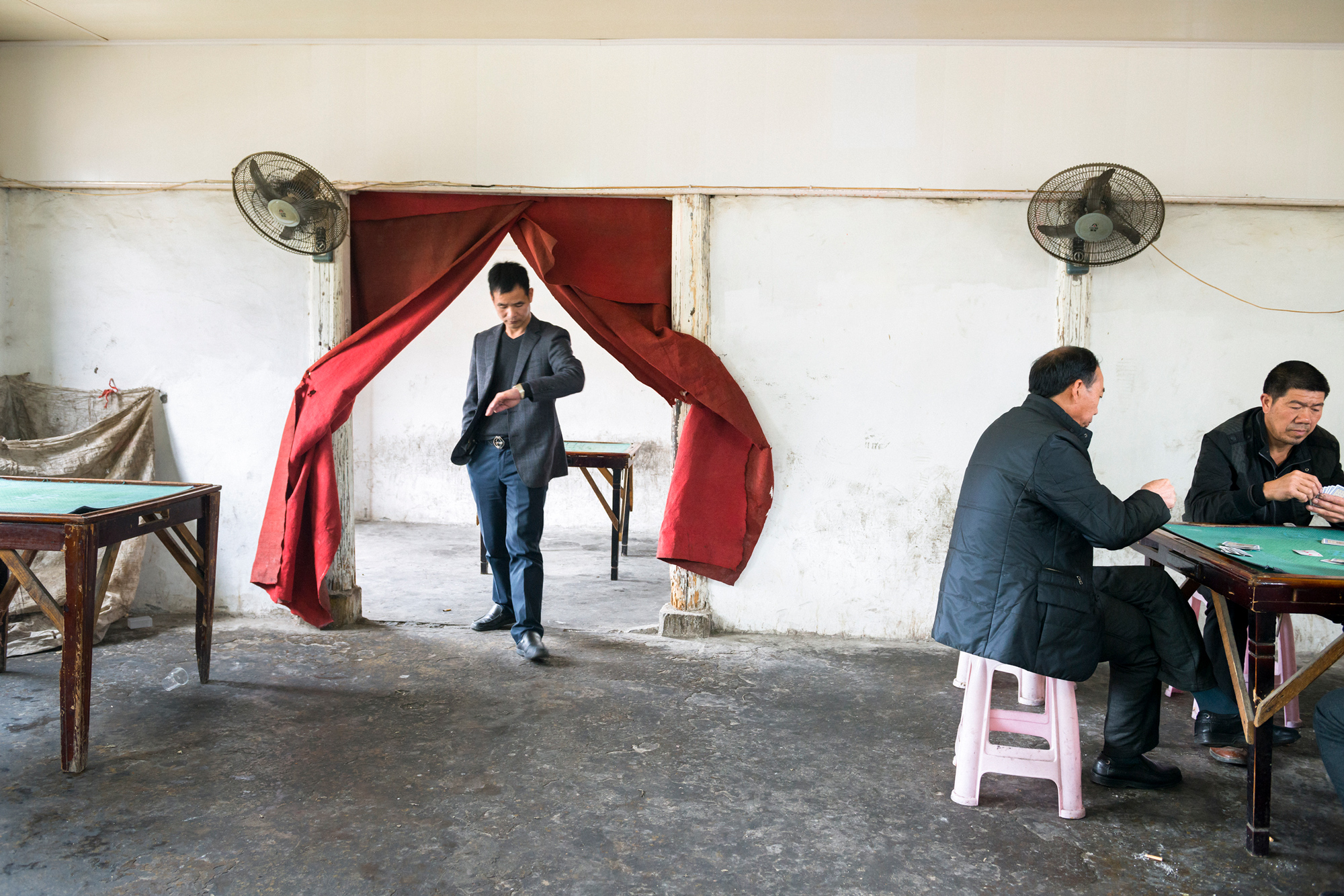 Villagers play poker at a board-game room in Xi'ao village in Tangxia township, March 17, 2013.