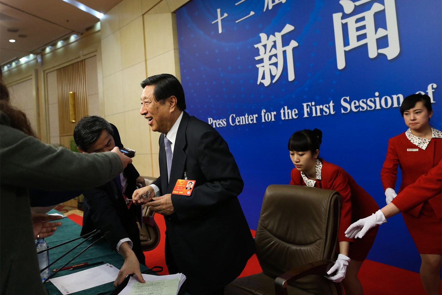 Female staff attend to Chongqing Mayor Huang Qifan during a press conference, March 4, 2011, at the Capital Hotel. Huang was close to the later disgraced Bo Xilai, who was Party Secretary of Chongqing at the time.