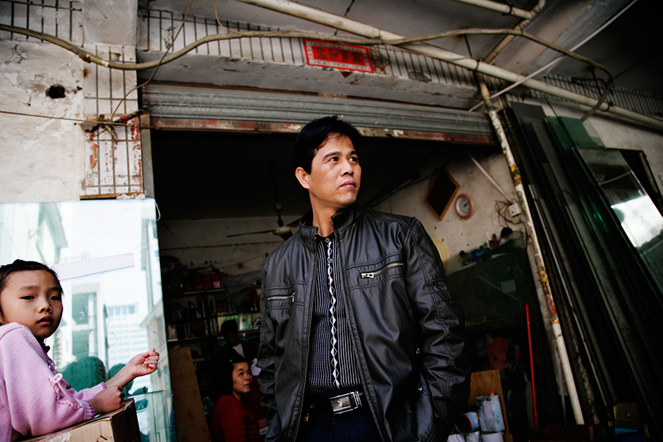 Mr. Li and his daughter stand in front of a neighbor's glass panel shop. They rented an apartment above the shop. Mr. Li and his wife came to Shenzhen from a rural village in Guangdong province as migrant workers twenty years ago, and their daughter was born in Shenzhen. However, without a Shenzhen <em>hukou</em> (official residence permit), the family is not eligible for government-sponsored housing, so this urban village existence has been the only source of affordable housing for them. The demolition of Gangxia West Village forced them to move to a smaller home in a new development.