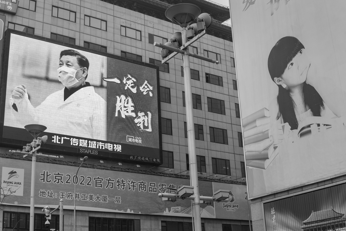"A billboard on Wangfujing Street shows a picture of Xi Jinping wearing a mask and lab coat, and the message ""We will win,"" February 20, 2020."
