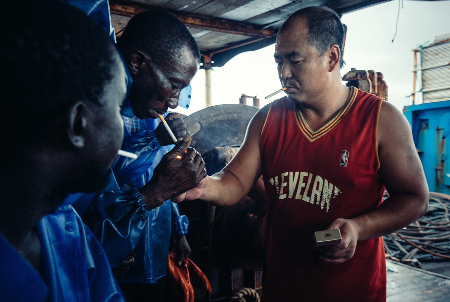 First Mate Wang passes cigarettes to a coworker on his ship, July 25, 2016. The African and Chinese crewmembers communicate through hand gestures and a handful of simple shared words and phrases.