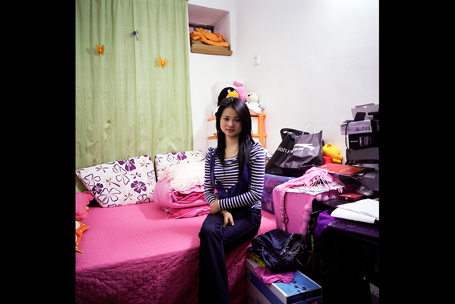 Ms. Zhou Hui poses for a portrait in her bedroom in Xiangxi Village. She paid US$150 in rent per month, for an apartment that she shared with a roommate. Ms. Zhou, who was born in 1986, is young, single, and moved to Shenzhen from a rural village in Hunan province in 2002. She was working in a luxury spa, saving most of her income with the hope of purchasing an apartment with her sister one day. However, her savings likely will not catch up to the pace of the rising cost of housing in Shenzhen, where today prices have reached US$4,800 per square meter in Ms. Zhou's neighborhood.