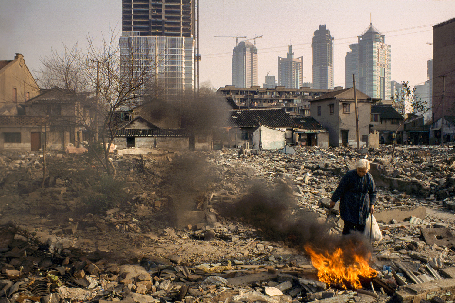 Preparing to vacate her home, an elderly resident burns discarded personal items, 1997.
