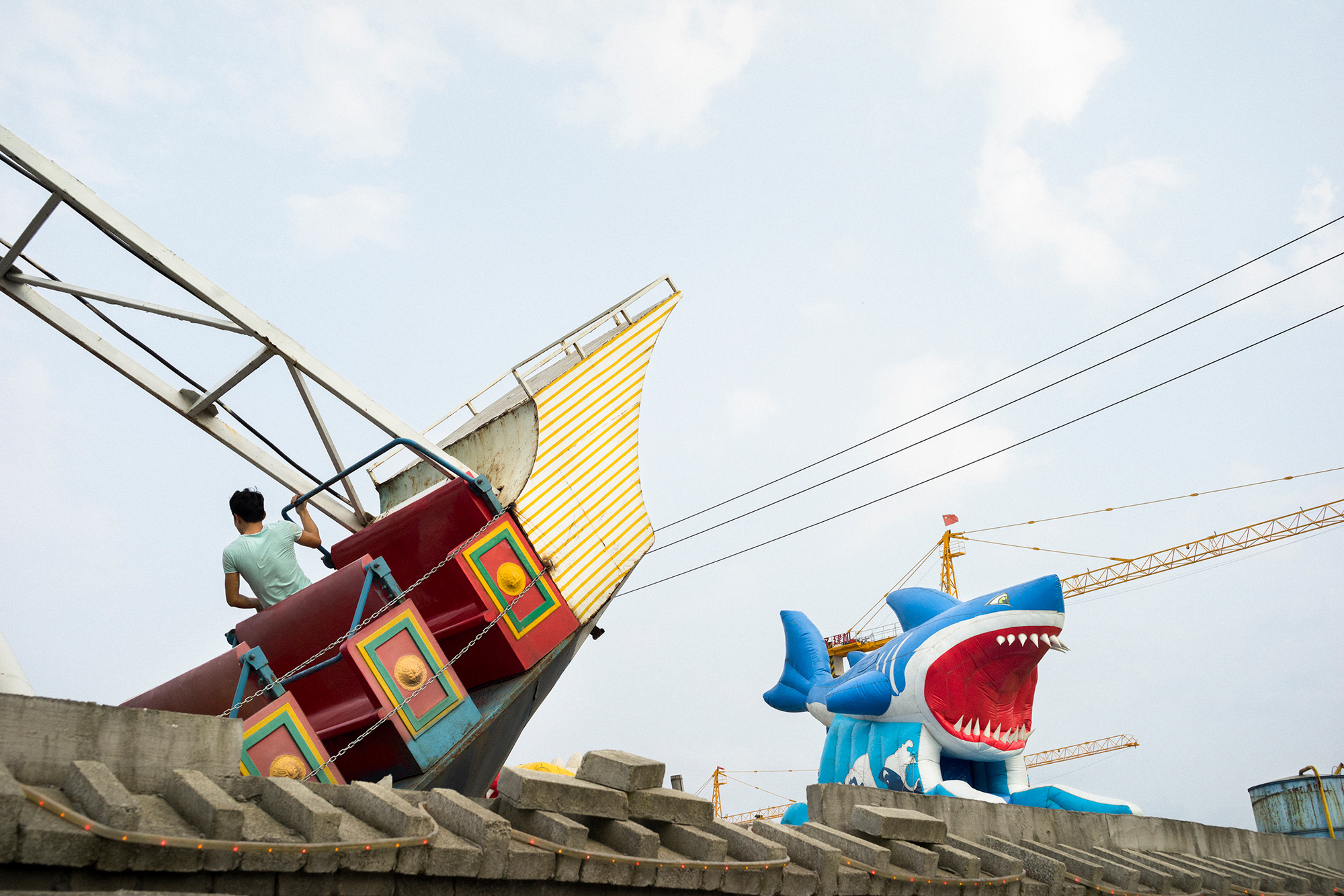 A man enjoys a ship-themed ride at a small amusement park on the former site of a farm in Feiyun, September 8, 2014. A residential complex is under construction beside the park.