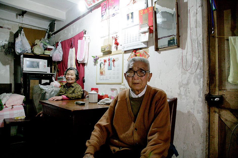 Ms. Qiao and Mr. Bao sit in their residence, a single room with no bathroom or kitchen, in Lane 1289 West Yan'an Road, Shanghai, June 3, 2009. They have lived in the same room for decades and cannot afford to move. The couple was hoping their home would be demolished and that they would receive compensation that would help pay for them to relocate to the suburbs of Shanghai.