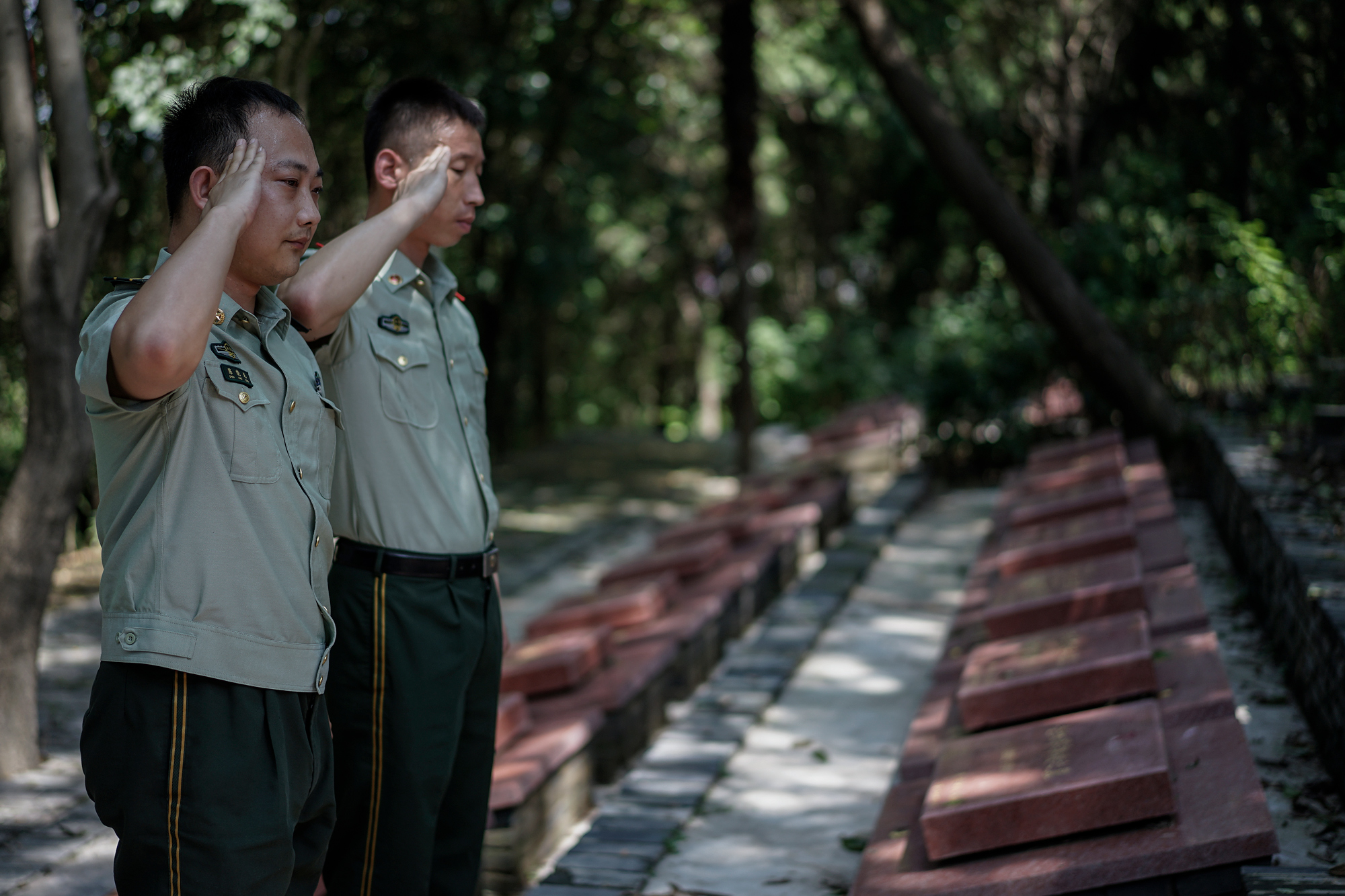 Ti's fellow firefighters salute his grave, at Martyrs' Cemetery in Suizhou, August 10, 2017.