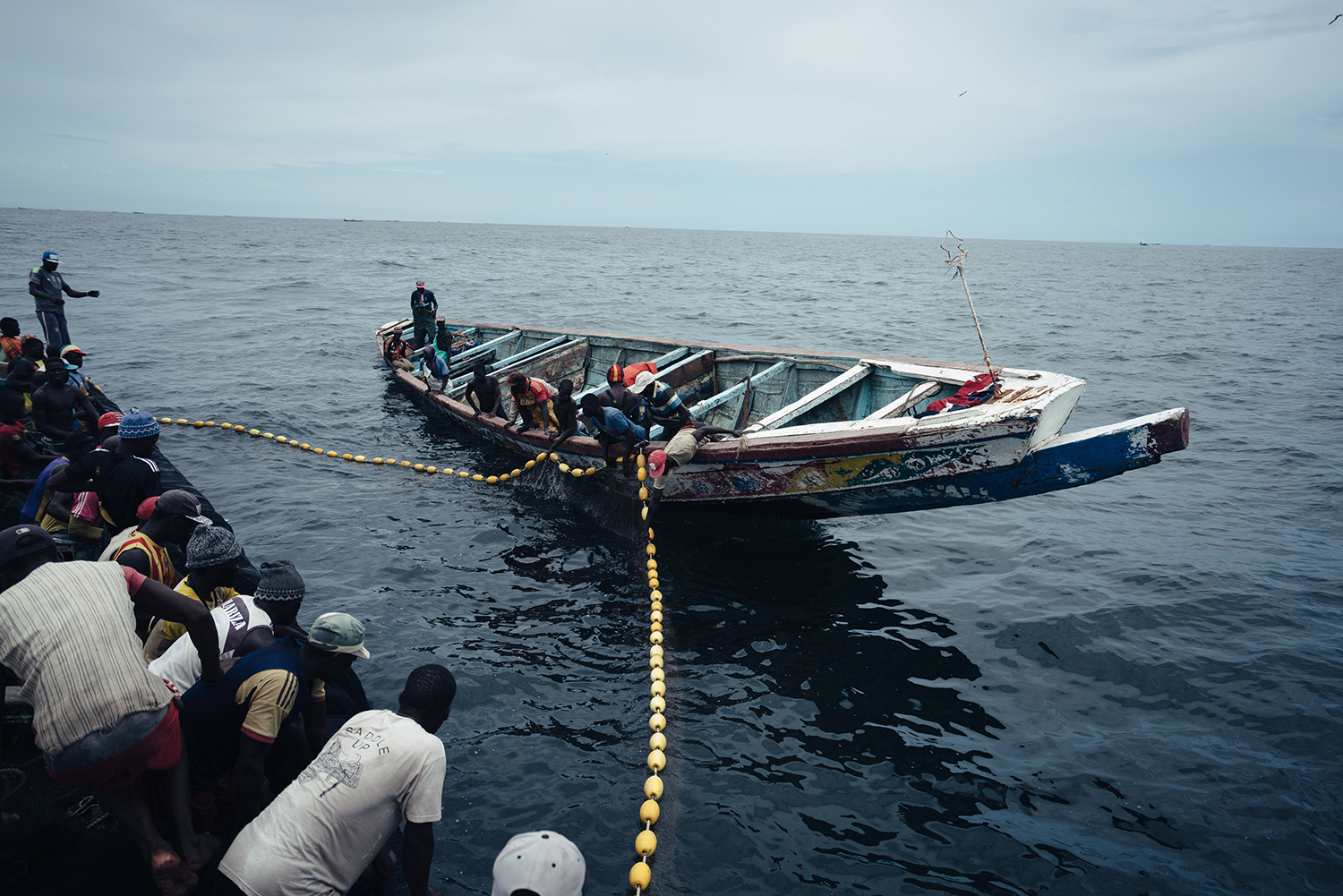 Local fishing methods operate on a much smaller scale than do Chinese industrial vessels. In Senegalese naval territory, a local fishing crew waits to draw in a net strung between two boats, July 15, 2016. Fishing and associated employment is a major source of jobs in Senegal, as well as a critical part of the economy.