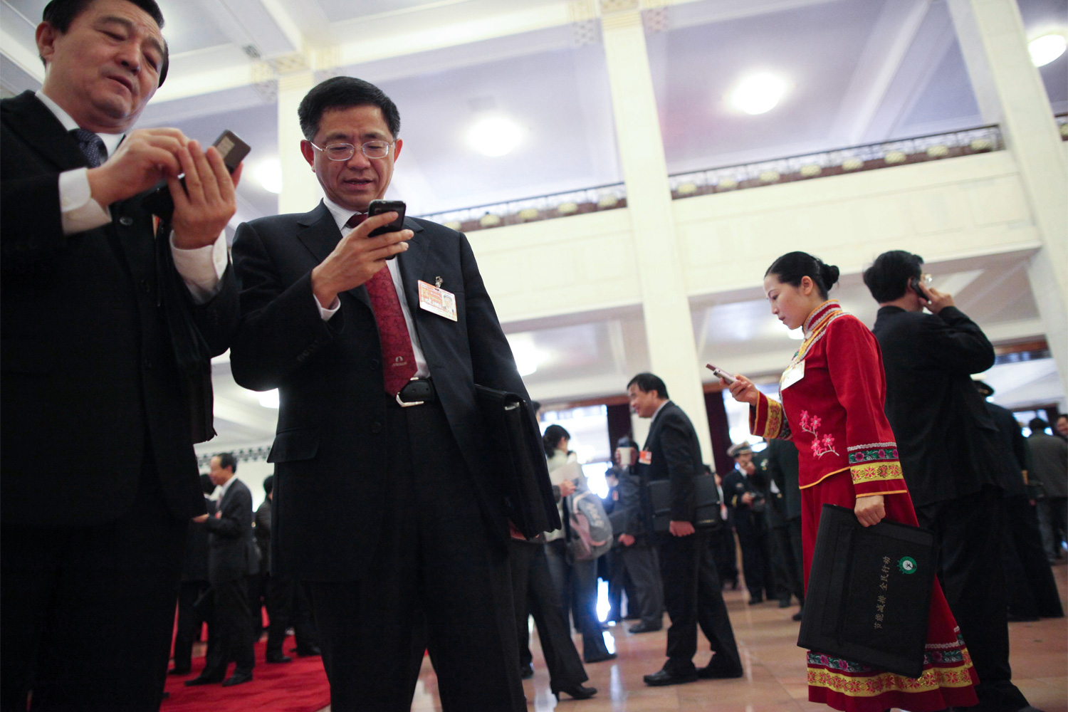 NPC members check their mobile phones, March 8, 2011, at the Great Hall of the People.