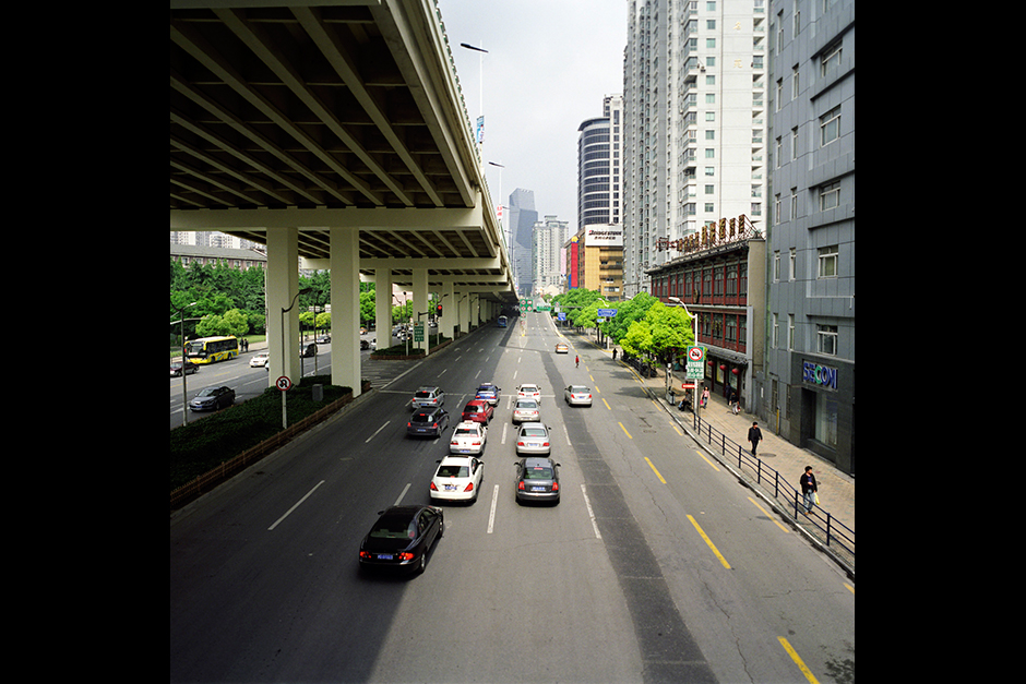 A shadow falls across West Yan'an Road, below, from the Yan'an Elevated Expressway. The municipality of Shanghai completed the construction of the expressway, which soars directly above the major thoroughfare of Yan'an Road, just four years after breaking ground in 1995. Although the elevated expressway connects with the existing road infrastructure, some residents complain that the expressway has deepened the isolation and invisibility of these neighborhoods.