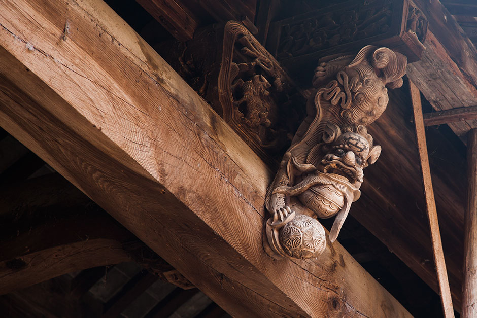 "A carved lion perches in the corner of Mingxian Hall's inner courtyard. During the Qing dynasty, when Mingxian Hall was built, the Huizhou region was known for its superior craftsmanship in stone, wood, brick, and ink slab carving. Some elderly villagers still refer to Mingxian as ""lion hall."""