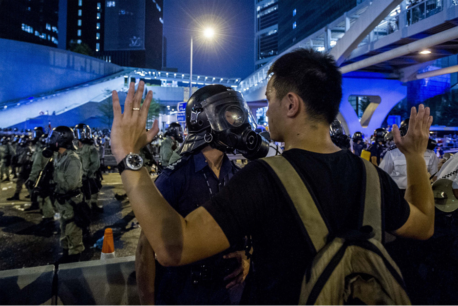 A pro-democracy protester faces a policeman. (Photo by Xaume Olleros/AFP/Getty Images)