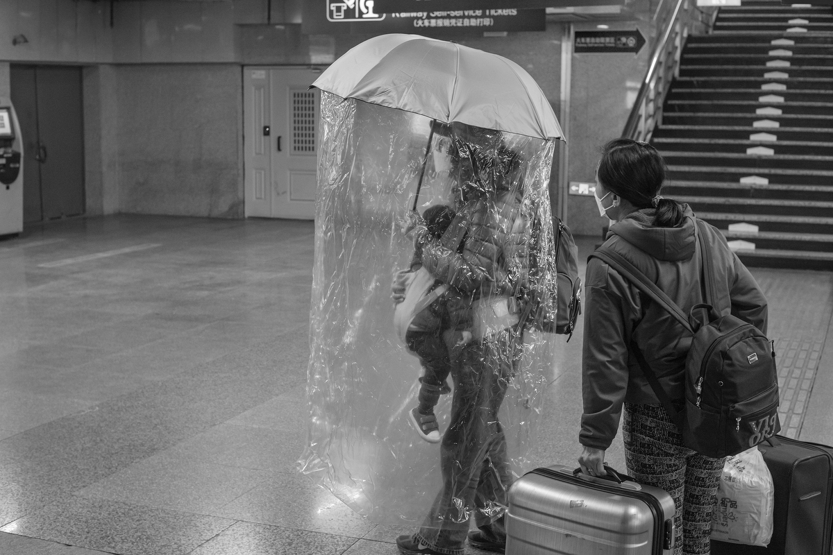 A parent carries an umbrella draped with a plastic sheet, enclosing them and their young child, Beijing West Railway Station, February 29, 2020.