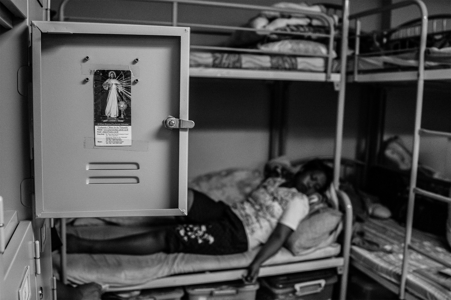 An image of Jesus Christ adorns a resident's locker as Sunarwi, an Indonesian domestic worker, rests after spending a day in court. She was accused of stealing 150 Canadian dollars from her former employer. Following a trial, a court later found Sunarwi guilty and sentenced her to a three-month prison term. Once foreign domestic workers have been sentenced and served out their jail terms, they are often deported and barred from returning to Hong Kong.