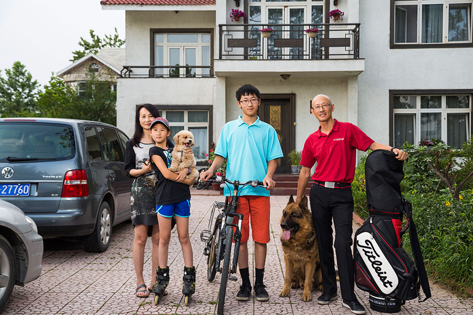 Wayne Ma, right, founder of Vision Golf Academy, stands with his family outside their million-dollar home in the suburbs of Beijing.