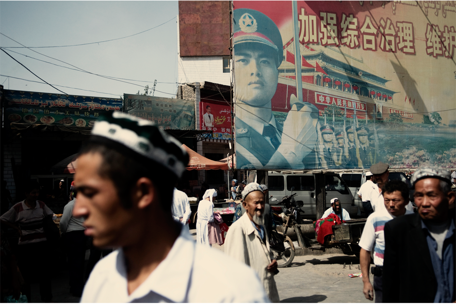 Uighurs pass by a propaganda poster featuring the People's Liberation Army in Kuqa, some 2,200 miles west of Beijing, in 2008.