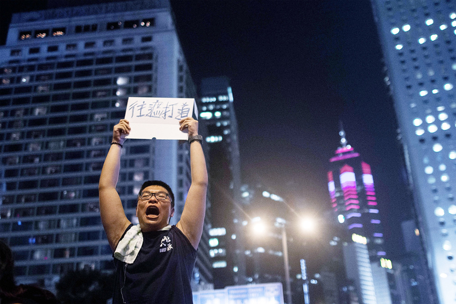 A protester instructs people to move to Chater Road in the Central District. (Photo by Anthony Kwan/Getty Images)