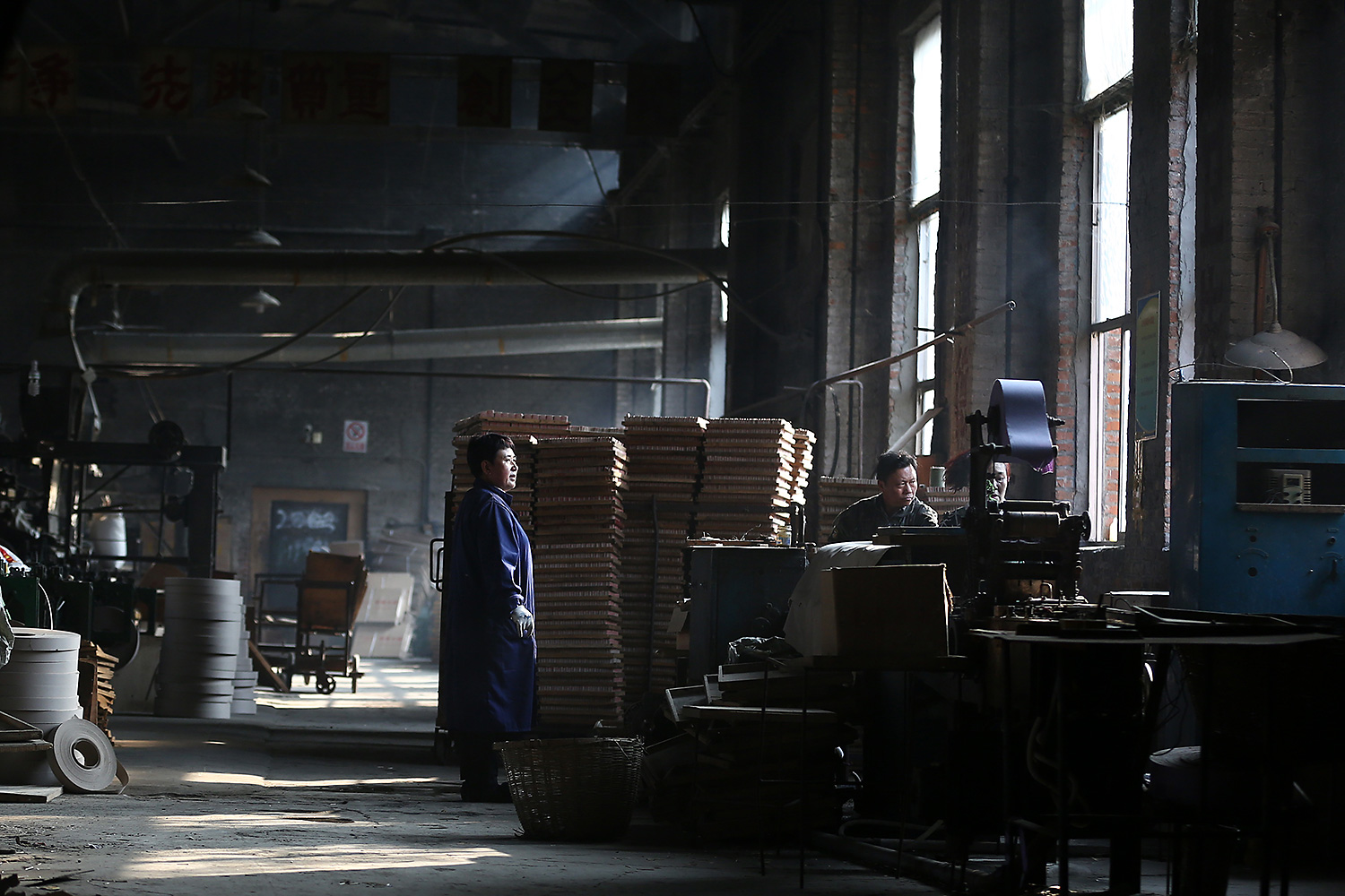 Factory Director Chu Junping, right, works with the old machines. With the factory's heyday long over, Chu says his business relies on old customers to keep it afloat.