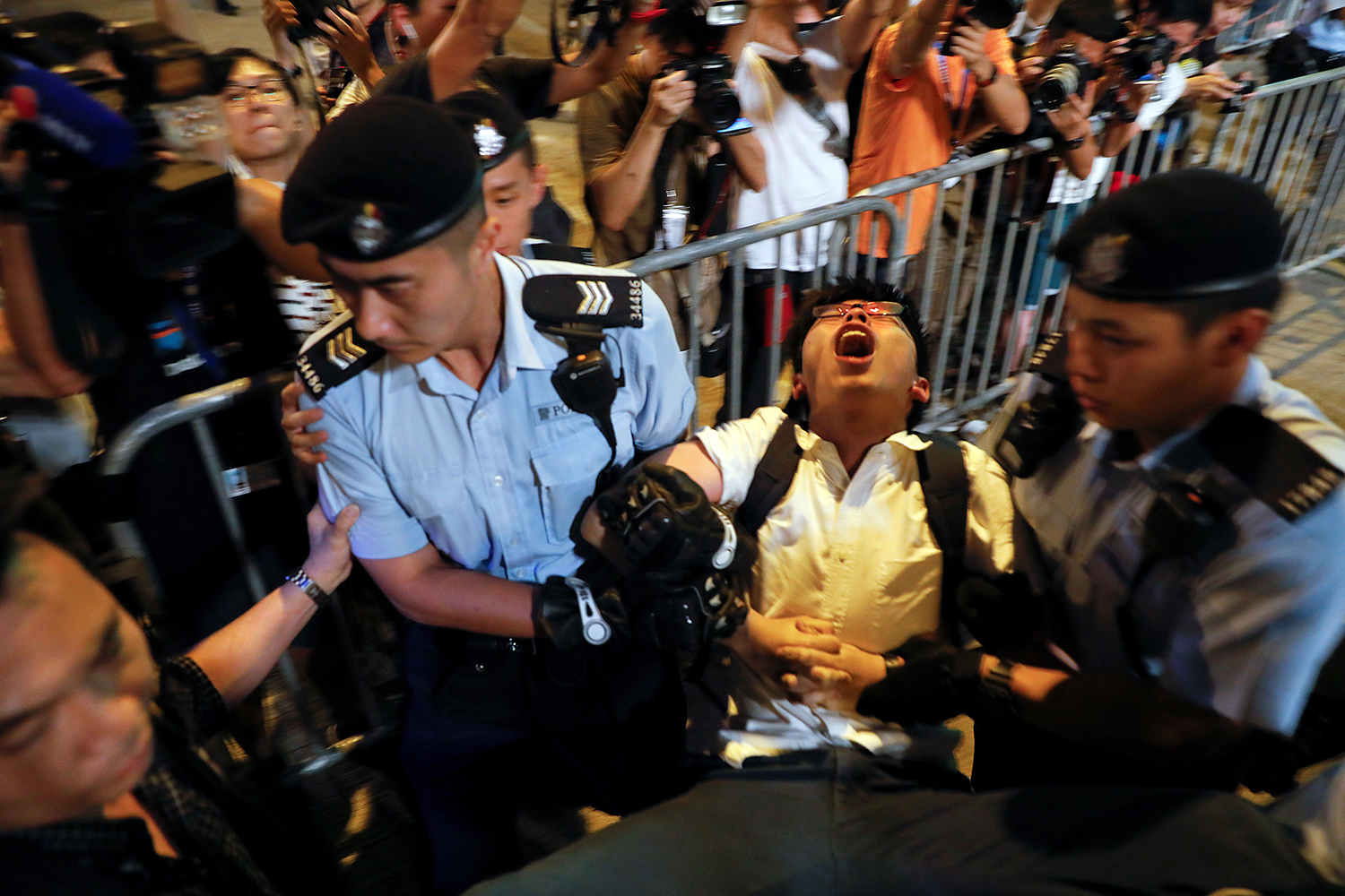 "June 28, student protest leader Joshua Wong shouts as he is carried by policemen while protesters are arrested at a monument commemorating the city's handover from British to Chinese rule, a day before Chinese President Xi Jinping is due to arrive to celebrate the handover's 20th anniversary, in Hong Kong. In August, Wong, Nathan Law, and Alex Chow were sentenced to prison for six to eight months in connection with their participation in 2014's ""Umbrella Movement."" (Damir Sagolj/Reuters)"