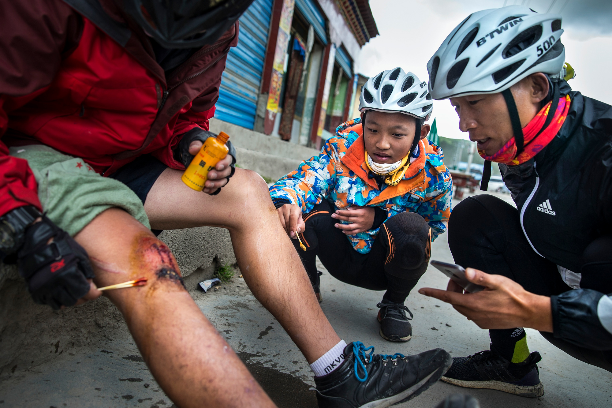 Chao and Runxi help an injured biker in Lhasa, Tibet, August 6.